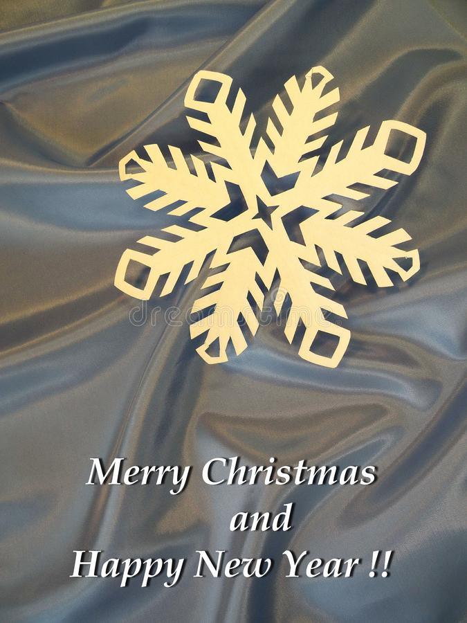 Merry Christmas and Happy New Year card done using paper snowflake , Lithuania. White paper snowflake on blue fabric and note - Merry Christmas and Happy New royalty free stock photos