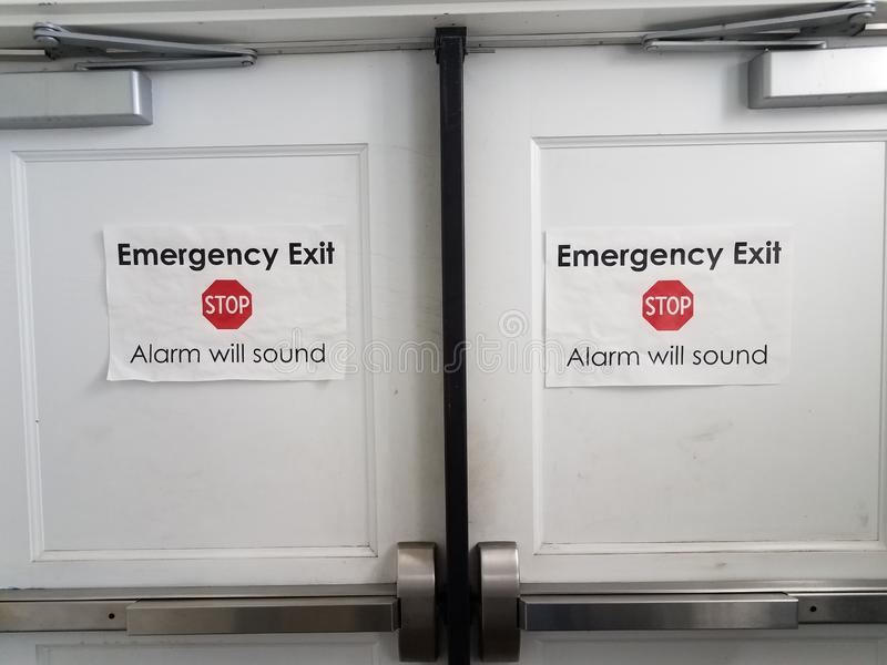 White paper stop emergency exit alarm will sound sign on door. White paper stop emergency exit alarm will sound sign on white door royalty free stock photos