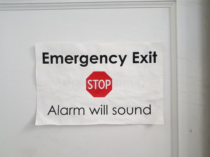 White paper stop emergency exit alarm will sound sign on door. White paper stop emergency exit alarm will sound sign on white door royalty free stock images