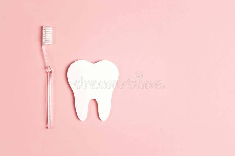 White paper tooth with toothbrush on pink background. Dental health concept. Flat lay, top view, copy space royalty free stock photos