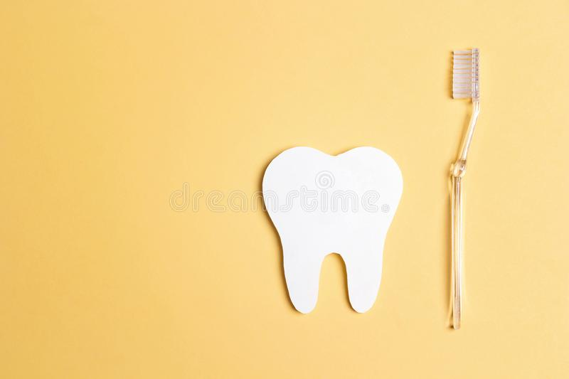White paper tooth with toothbrush on yellow background. Dental health concept. Dentist day concept stock image