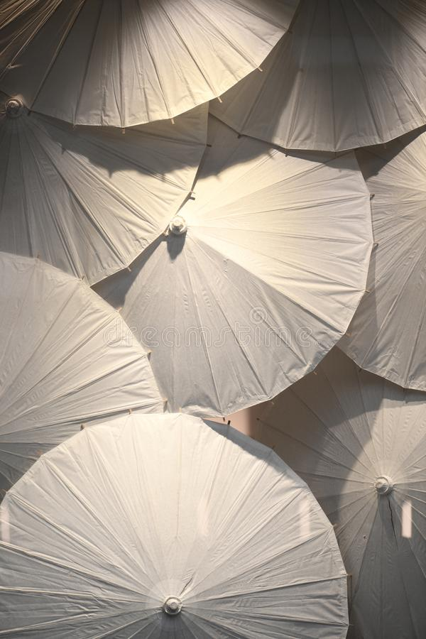 Decorative display of white paper umbrellas. White paper umbrellas displayed under directional lighting with sharp shadows stock images