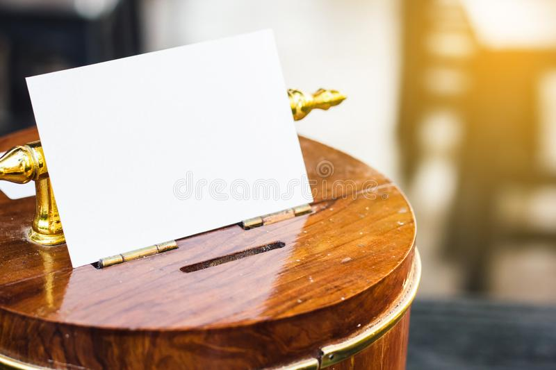 White paper on wooden piggy bank with light and copy space. Saving money concept. stock photography