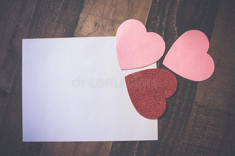 White paper on wooden table with three sparkly cutout hearts royalty free stock photo