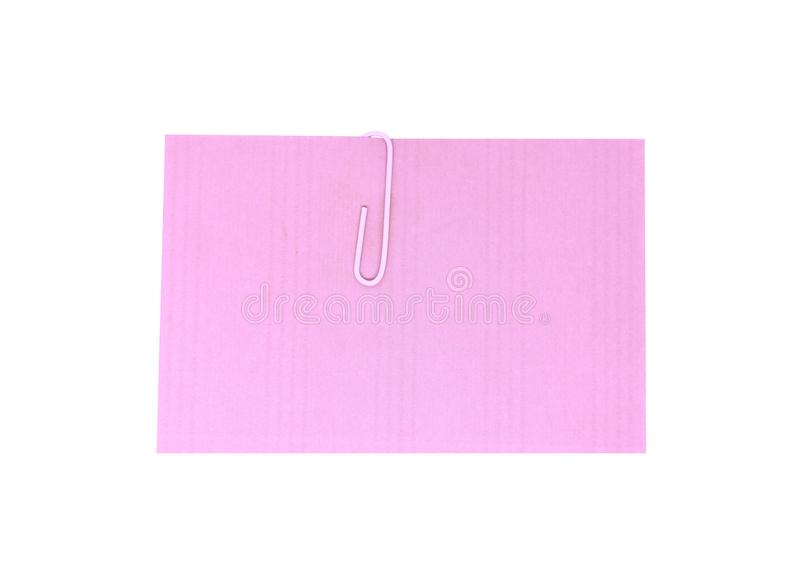 A white paperclip with blank pink notepaper. Pink sheet for your message or adding more text. Memo note with paper clip stock photography