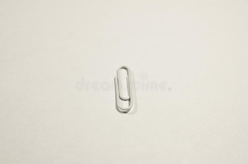 White paperclip. Isolated on the white background. School supplies and education stuff stock photography