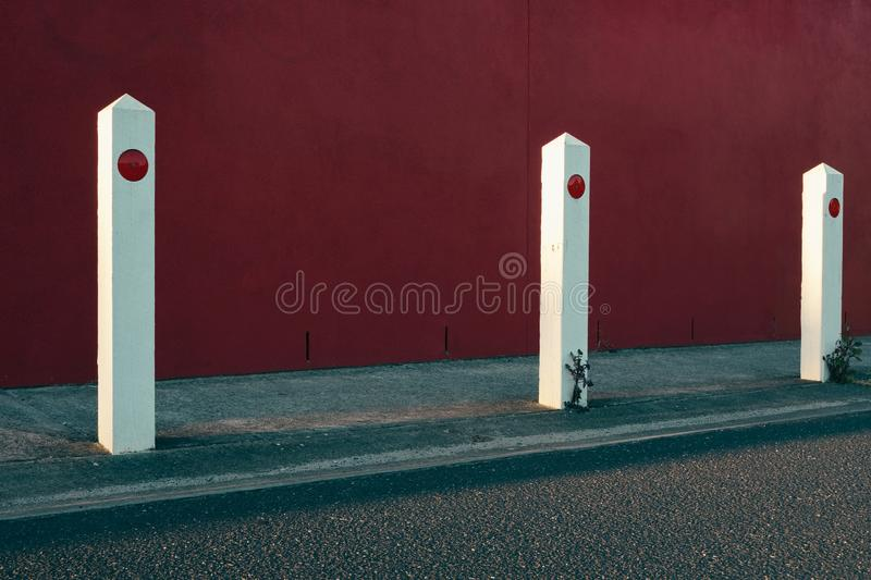 White parking poles alongside a road with a red wall in background royalty free stock photos