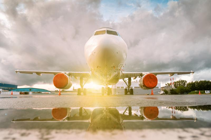 White passenger airplane parked near the hangars with reflection in a puddle at the setting evening sun. Front view royalty free stock photography