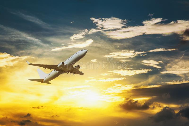 White passenger double decker plane in flight high above the golden clouds during the sunset stock photography