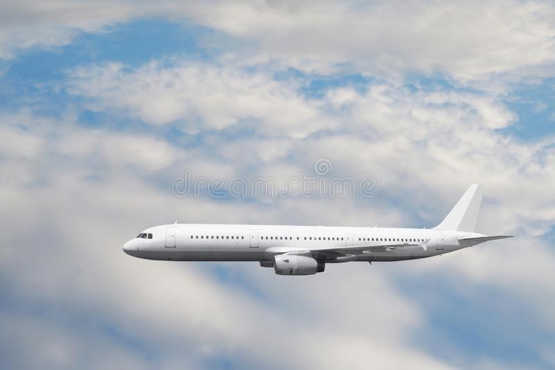 The white passenger plane flies against a slightly cloudy sky royalty free stock photos