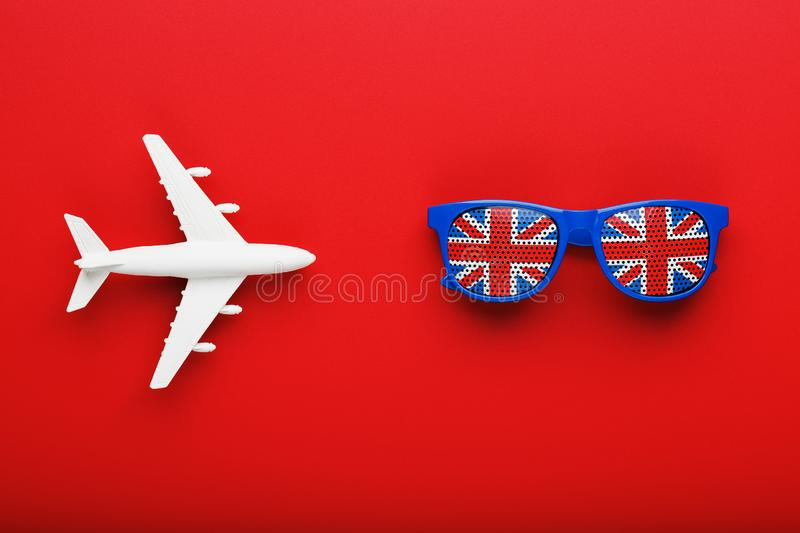 A white passenger plane flies in Sunglasses with the flag of the United Kingdom, on a red background royalty free stock images