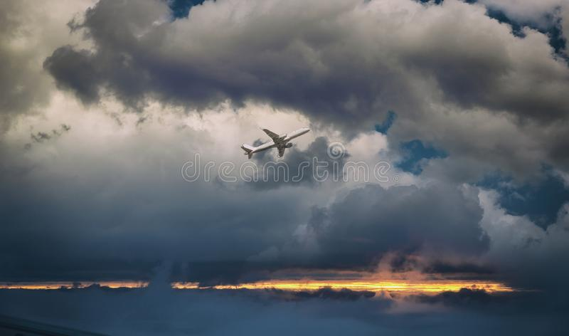 White passenger plane in flight. The plane flies against of sunset clouds. Aircraft side view. Passenger aircraft plane in flight against of sunset clouds side royalty free stock photo