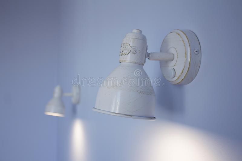 White patina metal lamps on a blue wall.  stock photography