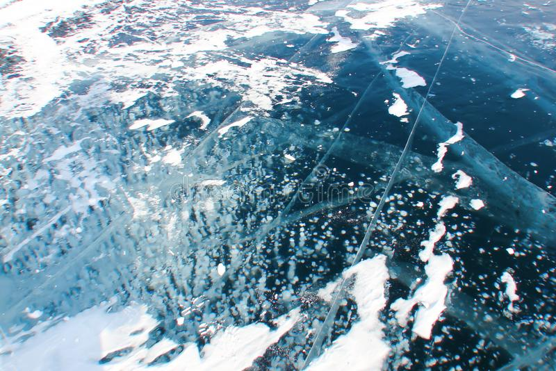 white pattern of frozen bubbles in thick dark-blue ice royalty free stock image