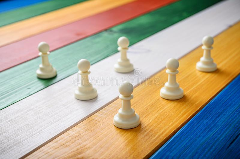 White pawn chess pieces. Placed on a coulourful desk of wooden planks stock photography