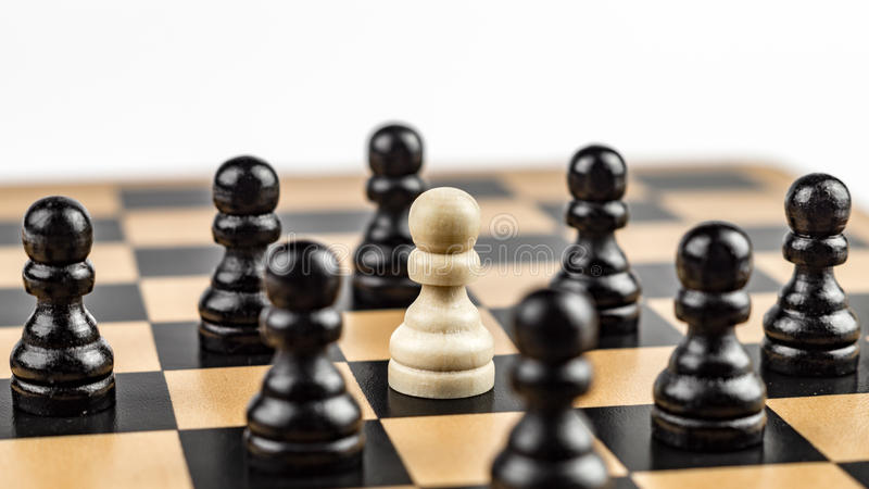 White Pawn surrounded by Enemies. White pawn threatened by black pawns stock image