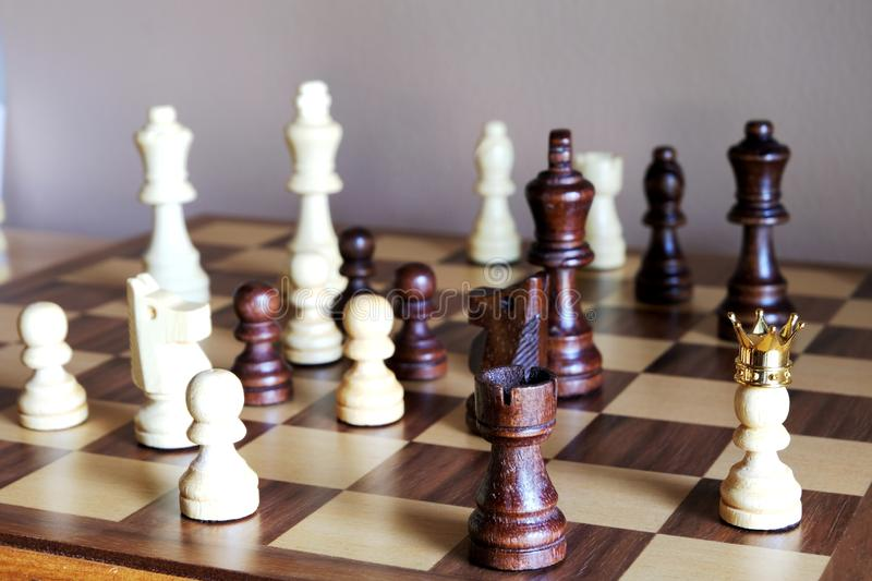 White pawn wearing crown stand among others and director of the team. Business leadership concept. Copy space royalty free stock photo