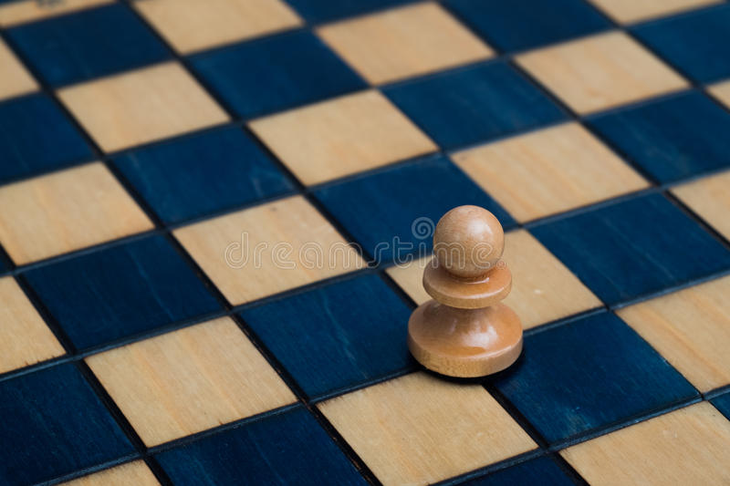 White pawn on wooden chessboard. Wooden white blue chess set royalty free stock photography