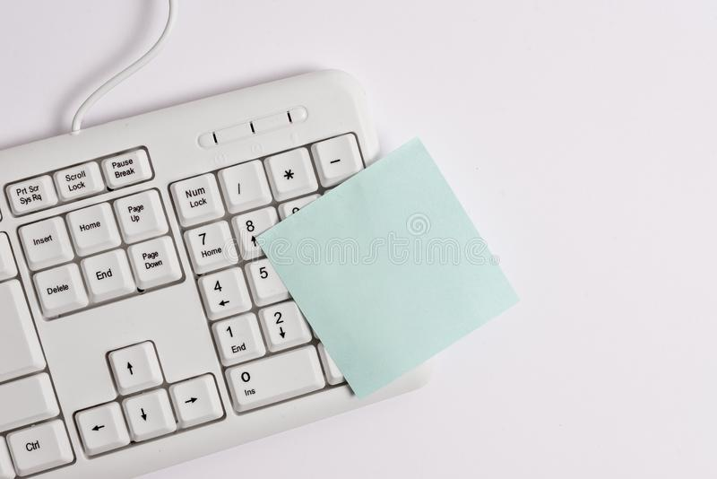 White pc keyboard with empty note paper above white background. Business concept with notes and pc keyboard. Blank paper royalty free stock images