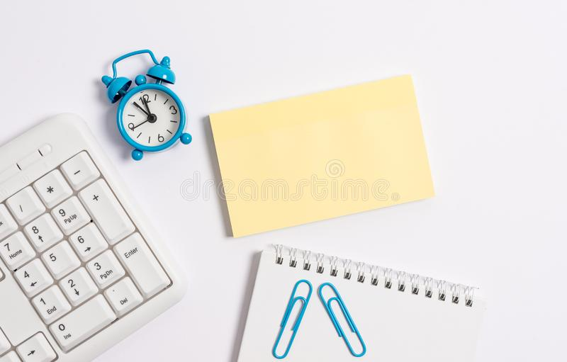 White pc keyboard with empty note paper and clock above white background. Business concept with notes and pc keyboard stock photo