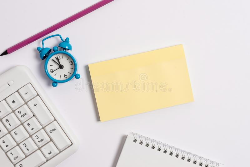White pc keyboard with empty note paper and clock above white background. Business concept with notes and pc keyboard royalty free stock image