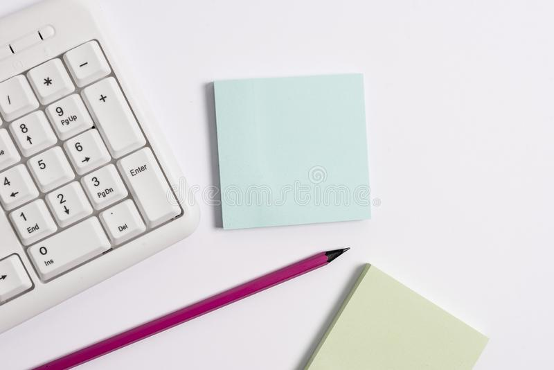 White pc keyboard with empty note paper and pencil above white background. Business concept with notes and pc keyboard royalty free stock photos