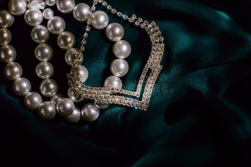 White pearl bracelet and necklace brilliant. White pearl bracelet and necklace brilliant on dark green velvet stock images
