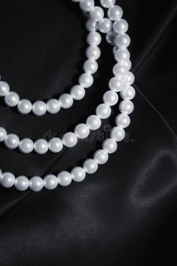 White pearl necklace on a black silk close up. Elegance white pearl necklace on a black silk extreme closeup stock photos