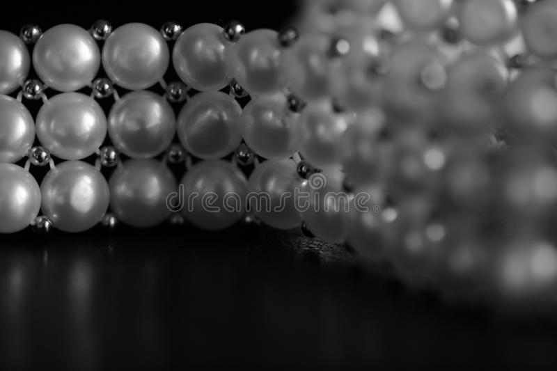White pearl necklace on a dark background. Black and white. White pearl necklace on a dark background close up. Black and white stock photography