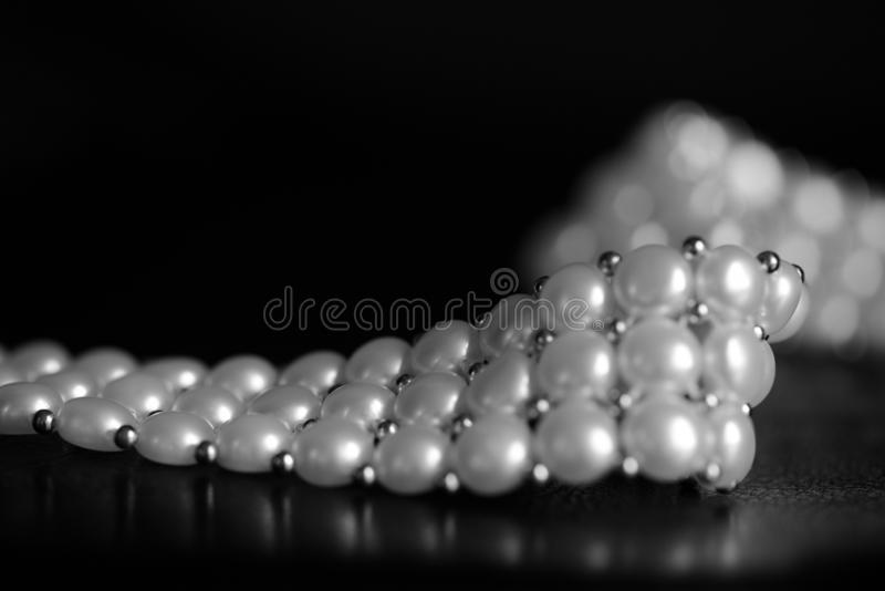 White pearl necklace on a dark background. Black and white. White pearl necklace on a dark background close up. Black and white royalty free stock images