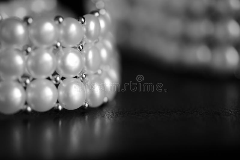 White pearl necklace on a dark background. Black and white. White pearl necklace on a dark background close up. Black and white royalty free stock photos