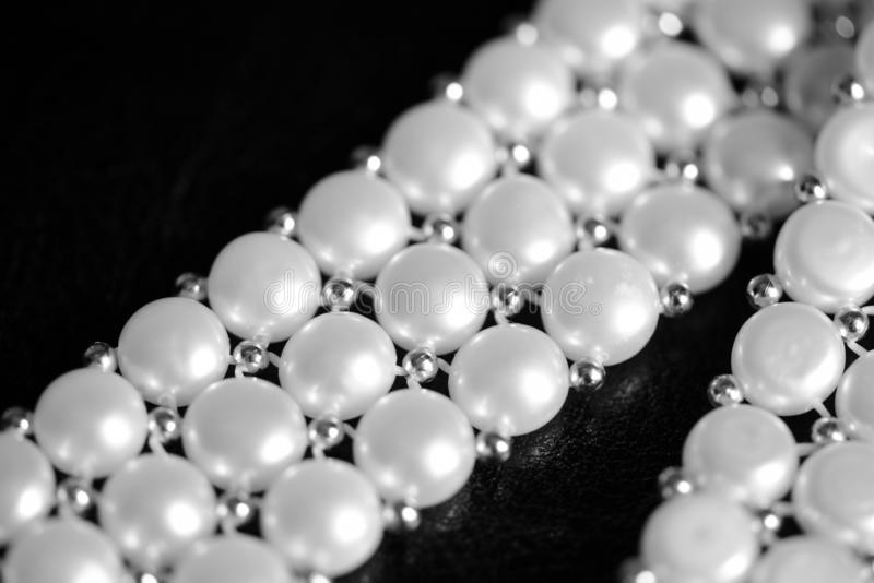 White pearl necklace on a dark background. Black and white. White pearl necklace on a dark background close up. Black and white stock photo