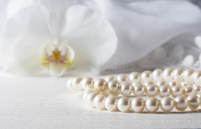 White pearl necklace on handmade lace background. selective focus. White pearl necklace on handmade lace background. Photo toned, selective focus stock photo