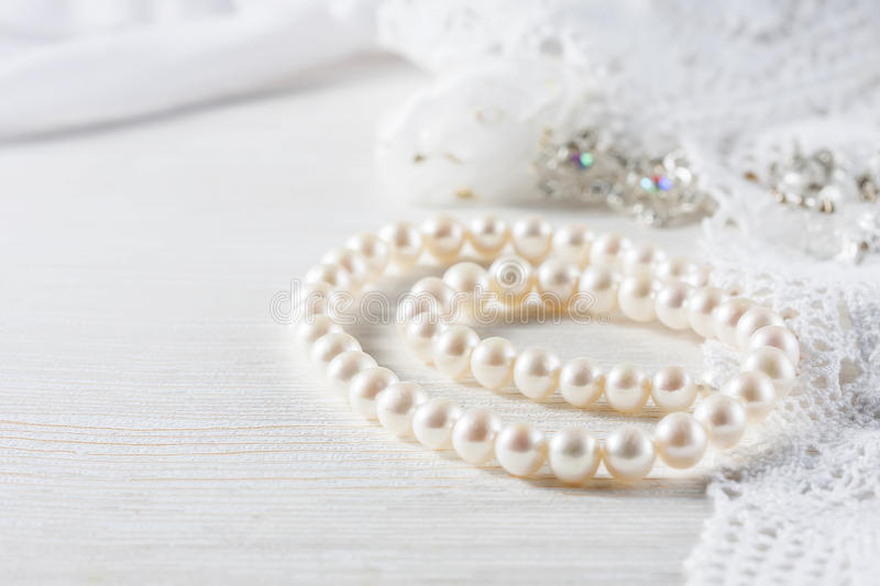 White pearl necklace on handmade lace background. Selective focus royalty free stock photo