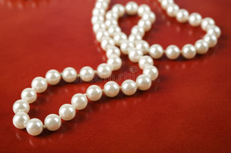 White pearl necklace on red background. Luxury white pearl necklace on reddish brown leather background stock image