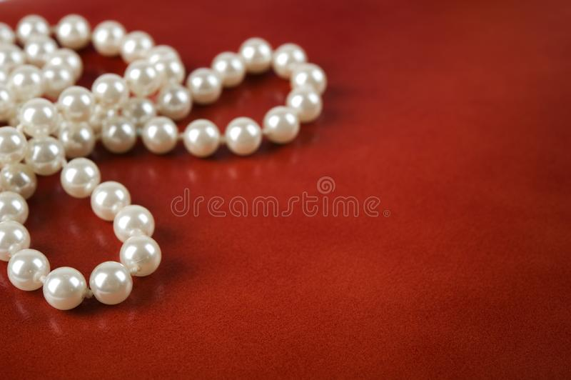 White pearl necklace on red background. Luxury white pearl necklace on reddish brown leather background royalty free stock images