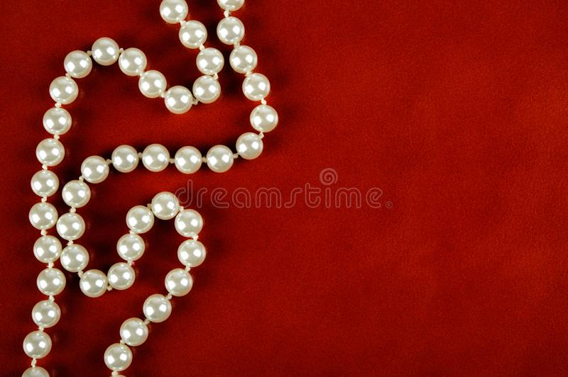 White pearl necklace on red background. Luxury white pearl necklace on reddish brown leather background stock images