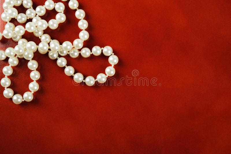 White pearl necklace on red background. Luxury white pearl necklace on reddish brown leather background royalty free stock photo