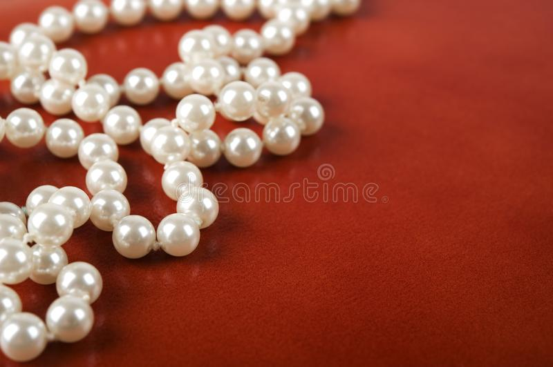 White pearl necklace on red background. Luxury white pearl necklace on reddish brown leather background. Selective focus stock images