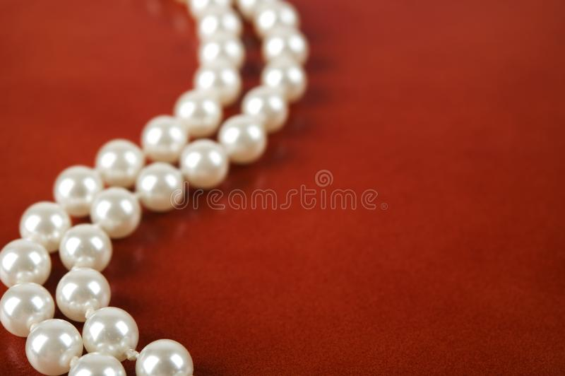 White pearl necklace on red background. Luxury white pearl necklace on reddish brown leather background. Selective focus stock image