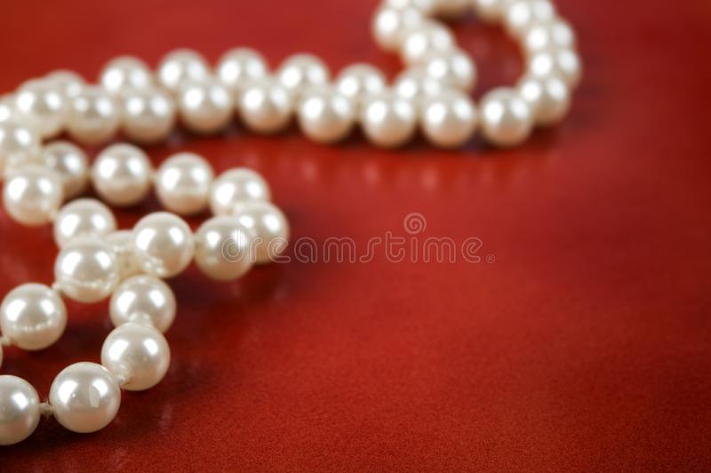 White pearl necklace on red background. Luxury white pearl necklace on reddish brown leather background. Selective focus royalty free stock photos