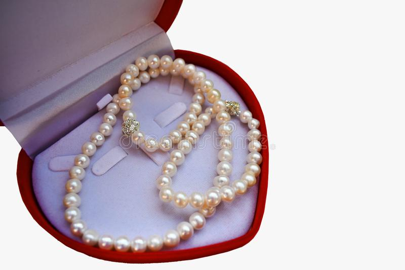 White pearl necklace on a red box is a heart shape. stock photos