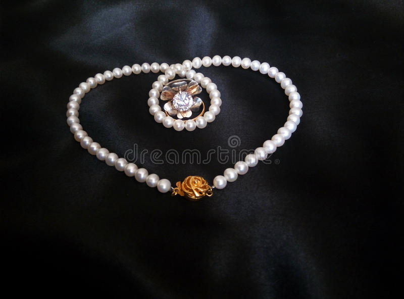 White pearl necklace with rings on black silky background royalty free stock photo