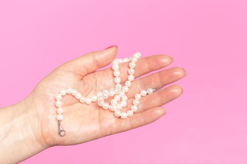White pearl necklace on the woman`s hand stock photography