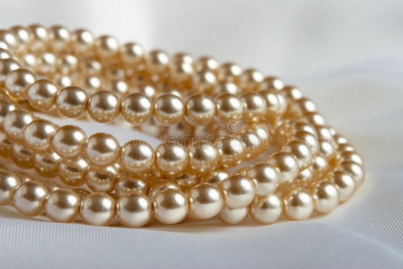 White Pearls. Strings on a piece of silk stock images