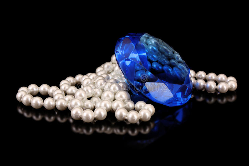White pearls with big blue gem. On black royalty free stock image