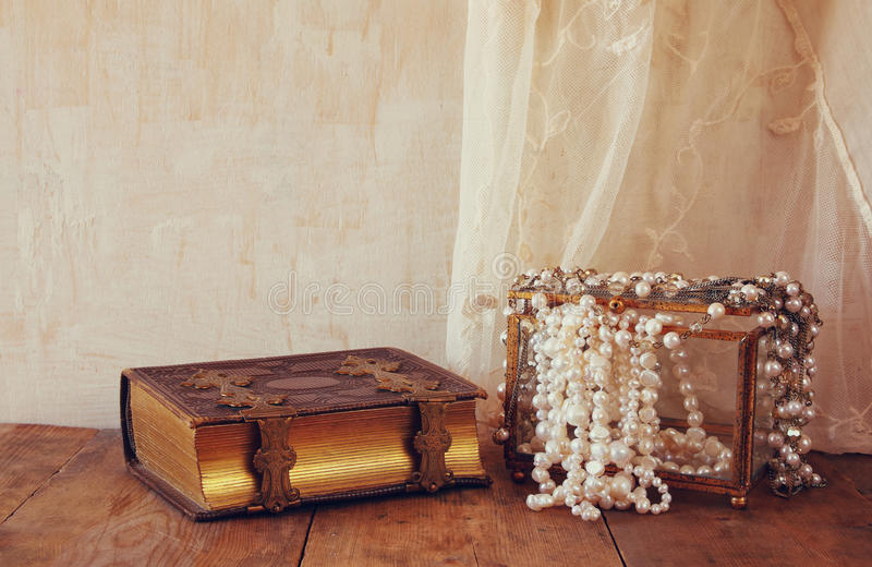 White pearls necklace and old book on old wooden table royalty free stock photography