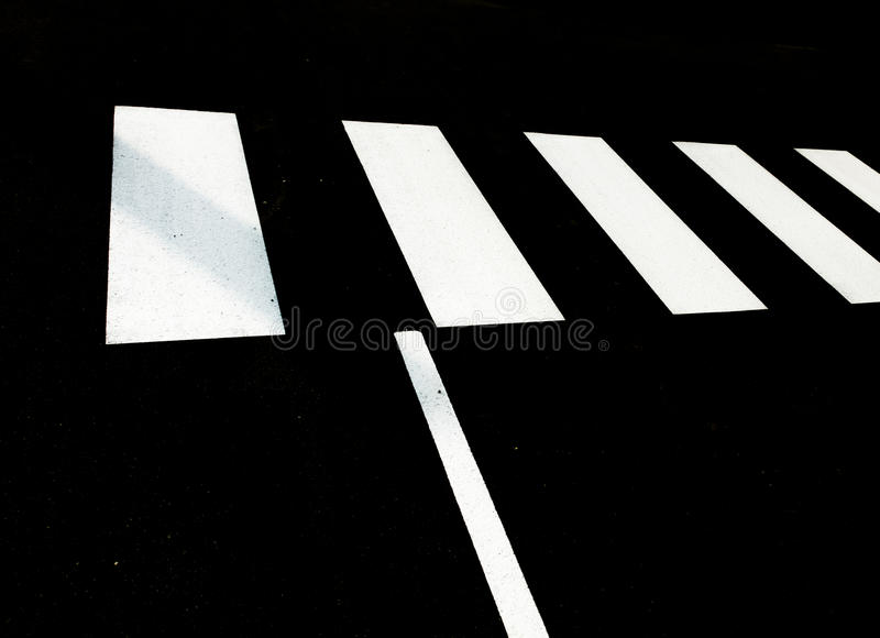 White pedestrian crossing on black tar stock images