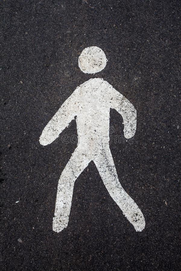 A white pedestrian sign on the road. A white airbrushed pedestrian sign painted on the asphalt of a street royalty free stock photo