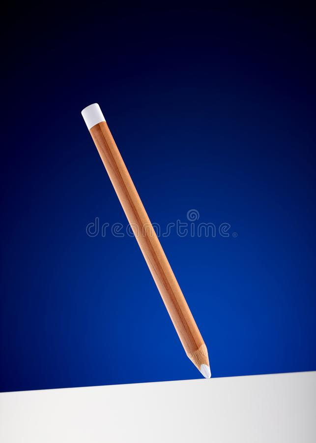 White pencil hanging on the air drawing a thick white line royalty free stock images
